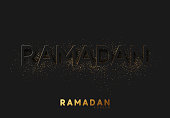 Ramadan Kareem black background with embossment text sprinkled with golden shiny powder of dust and sand.