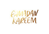 Ramadan Kareem. Text golden handwritten calligraphy. Lettering isolated on white background