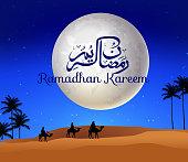 Ramadan kareem with walking camel caravan in the desert
