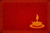 Dark red grunge background with . Slightly lighter tone mitti ka diya or Deepak with a flame or lau objects in small size. Can be used as Diwali wallpaper, background or gift wrapping sheet. New Year happy festive background. No text. No people. Grungy, smudged, abrasive sandpaper effect ,texture. New Year's eve, Pooja, prayer, prayers, house warming or inauguration, birthday party festive celebration theme. No people. No text.
