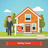 Real estate broker and house with for sale sign