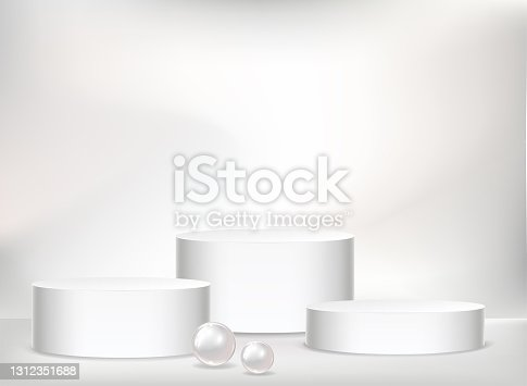 istock Realistic vector cylindric podium for your product design. Template contains three empty stages, light effects and pearls 1312351688
