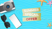 Creative illustration summer sale banner with sun glasses, camera, smartphone display, star fish on blue wood background paper cut style. Poster, advertising, postcard, flyer, brochure template.