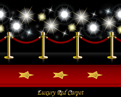 Red Carpet Decorated with Golden Stars lying on the Floor in front of Poles with Barrier Rope and Paparazzi Flashes