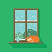 istock Red cat is sleeping and a cup of hot coffee or tea is standing on the windowsill 1057893090