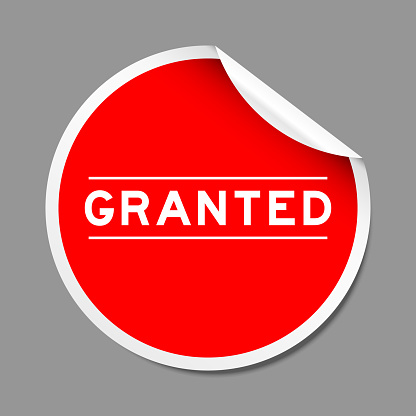 Red color peel sticker label with word granted on gray background