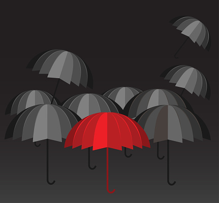 Red umbrella and a crowd of black ones
