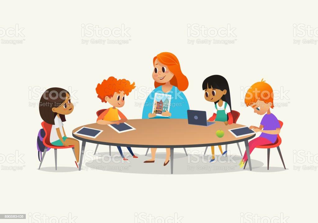 39b57799a60c38 Roodharige vrouwelijke leraar weergegeven: foto kinderen zitten rond de  ronde tafel op klasse met laptop