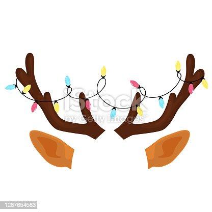 istock Reindeer antlers with Christmas light garland. Funny selfie photo mask 1287654583