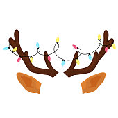istock Reindeer antlers with Christmas light garland. Funny selfie photo mask 1287654583