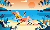 istock Retired old man on beach enjoying life with a book in hand 1192660201