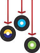 Vector illustration of three 45 rpm christmas ornaments hanging from shiny red ribbons.