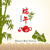 Celebrating the Dragon Boat Festival with rice dumpling and tea on the background of bamboo and wave pattern