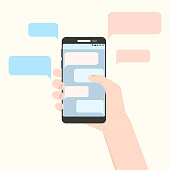 Right hand holding smartphone with pink and blue message clouds. European handle mobile phone with his finger touching screen with discussion bubbles