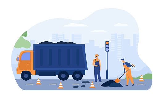 Road workers spreading asphalt on street