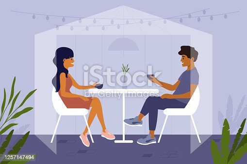 istock Romantic couple sit at cafe inside safety glass cabin and drink coffee or tea 1257147494