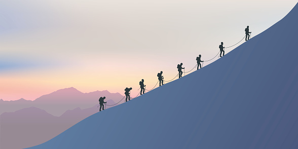 Roped climbers climb the side of a mountain as they walk along a ridge at sunset.