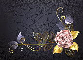 Sparkling rose of pink gold, decorated with gold leaves on a black textured background. Pink gold. Design with roses.