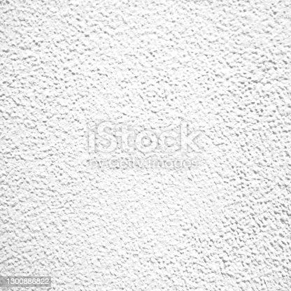 istock Rough white relief stucco wall texture background in close up 1300886822