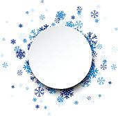 Round paper card over blue snowflakes.