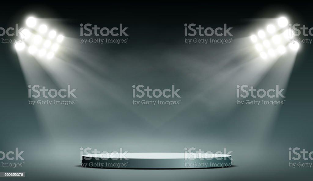 Round podium illuminated by searchlights.