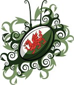 A decorative rugby emblem. Contains a  rugby ball sporting the Welsh flag. Surrounding pattern consisting of dragons tails.