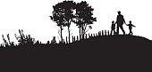 A vector silhouette illustration of a family going on a walk in the countryside