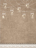 Rustic burlap background with string lights and lace