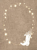 Vector illustration of a Rustic burlap background with string lights and cowboy boot with flowers. Easy to edit.