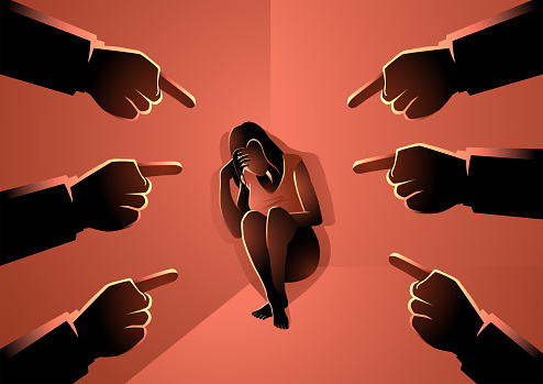 Sad or depressed woman sitting cornered surrounded by pointing hands