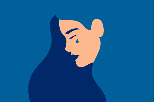 Sad young girl is crying on a blue background.