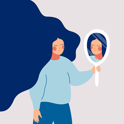 Sad young woman looks on her reflection in mirror with sorrow