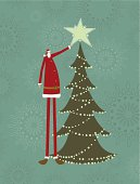 Vintage card with Santa putting a star on top of the christmas tree. He is as tall as the tree.
