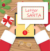 Santa claus is sitting at his workplace desk and receiving one message on his tablet