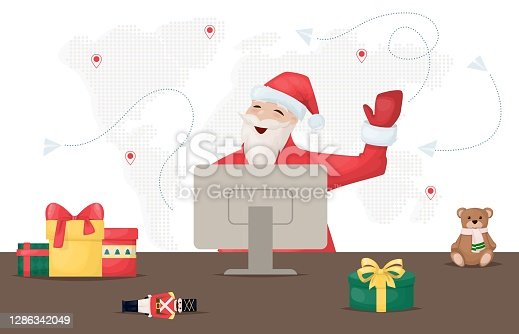 istock Santa Claus work online on his computer. World map. Santa is looking for gifts on Internet 1286342049