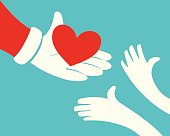 Close up of Santa claus hand holding red heart and hands of children on green background