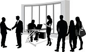 A vector silhouette illustration of a busy school office with several people going about their business including young men greeting shaking hands, a man working at a desk computer, a young woman using her cell phone, and a group of three male and female students standing and socializing.