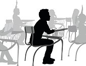 A vector silhouette illustration of a young boy sitting at his desk in a grade school classroom listening and taking notes.