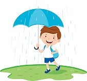 School boy with umbrella in the rain