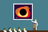 A scientist discusses a picture of a black hole