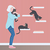 Vector illustration of a senior woman holding and kissing one of her cats while two more black cats sit on and walk the cat wall shelves. The white haired senior is wearing pink and blue star leggings, pink sneakers, and a light blue shirt.