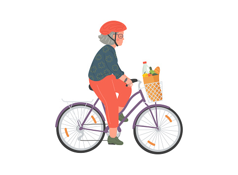 Senior woman cycles on bicycle with basket