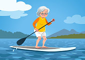 Senior woman on a stand up paddle board. Cute grandma wearing rash guard and shorts paddling on calm water, trees and mountains in the background. Healthy active lifestyle, water sports for seniors.