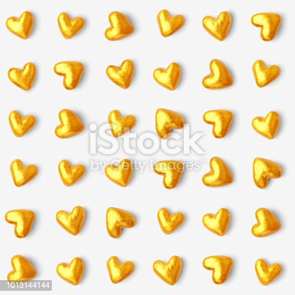 A collection of golden hearts. Beautiful stylish and modern design of small hearts in a row isolated on white piece of paper.  Hearts resemble luxury chocolates packed in golden tin foil papers. Hand-made realistic illustration in vector.  Zoom to see the details.  Original stylish design associated with opulence, wealth and luxury. Artwork full of depth, glamor and glow. Isolated design object.