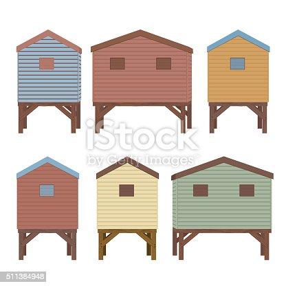 Pastel colored wooden beach huts. The huts are all on wood stilts and have ship lap sided walls. Back view.