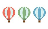 Set of colorful hot air balloons of red green and blue colors with a basket and ropes isolated on white background - vector