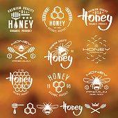 Set of honey labels, badges, logotypes and design elements. White print on blurred background