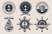 Set of nautical badges with steering wheel, anchor, seashell on a dark background. The text for each badge is on a separate group.