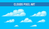 Set of pixel clouds with dithering effect on blue background. Old school computer graphic style.