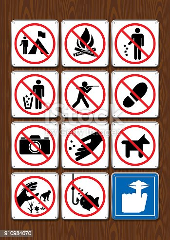 istock Set of prohibitive icons of not camping, no bonfire, littering, hunting,  stepping, fishing, silence. Icons in blue color on wooden background 910984070